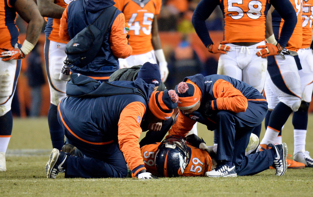 . Denver Broncos outside linebacker Danny Trevathan (59) is checked on the field during the second half.  The Denver Broncos vs. the San Diego Chargers at Sports Authority Field at Mile High in Denver on December 12, 2013. (Photo by Hyoung Chang/The Denver Post)