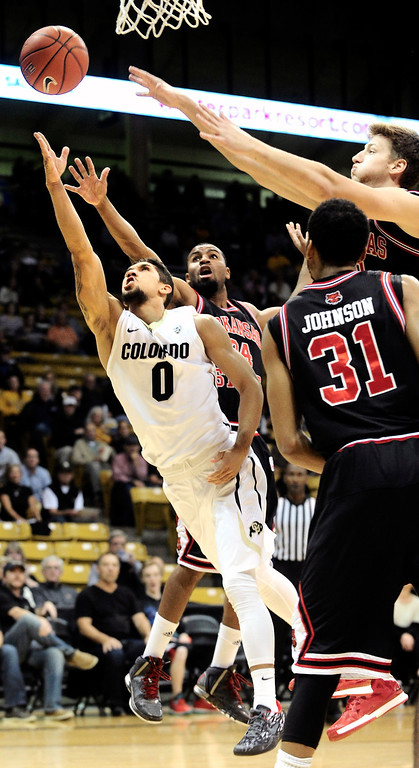 . University of Colorado\'s Askia Booker (0) goes to the hoop against Arkansas State\'s Ed Townsel (24) and Melvin Johnson (31) during their game at the Coors Events Center on the CU Boulder Campus in Boulder, Colorado on November 18, 2013.  Photo by Paul Aiken / The Boulder Daily Camera.