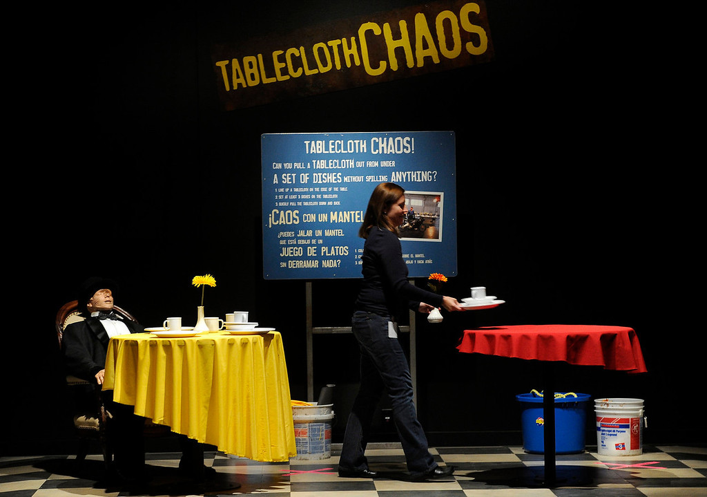 . Lisa Decker, manager of temporary exhibitions, places the plates and cups on the tables at Tablecloth Chaos. The Denver Museum of Nature and Science hosts MythBusters: The Explosive Exhibition which opens to the public Oct. 11 and  runs through Jan. 5, 2014. The exhibit uses interactive technology that allows visitors to spend the day as a MythBuster using the same methods as the hosts of Discovery Channel�s series MythBusters. Guest can experiment with Running in the Rain, Blind Driving, and Killer Card Toss. (Photo By Kathryn Scott Osler/The Denver Post)