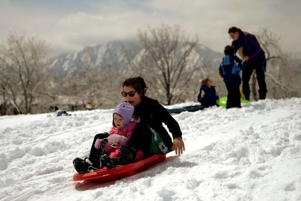 . BOULDER, CO. - APRIL 23: 4 year old Megan Doyle rides with her mom Lily heading to the bottom of the hill as they sleds at Scott Carpenter Park April 23, 2013 Boulder, Colorado. (Photo By Joe Amon/The Denver Post)