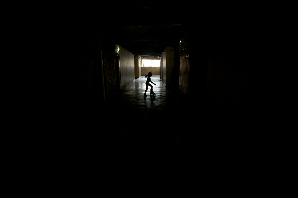 . A girl skates in the abandoned halls inside the the worldís tallest slum, the Tower of David, a half-built skyscraper that was abandoned in the 1990s and was transformed by squatters into a vertical ghetto, in Caracas, Venezuela, Tuesday, July 22, 2014. Officials and armed soldiers began moving out the first of thousands of squatters who have lived for nearly a decade in a soaring, half-built skyscraper in the heart of Caracas. (AP Photo/Fernando Llano)