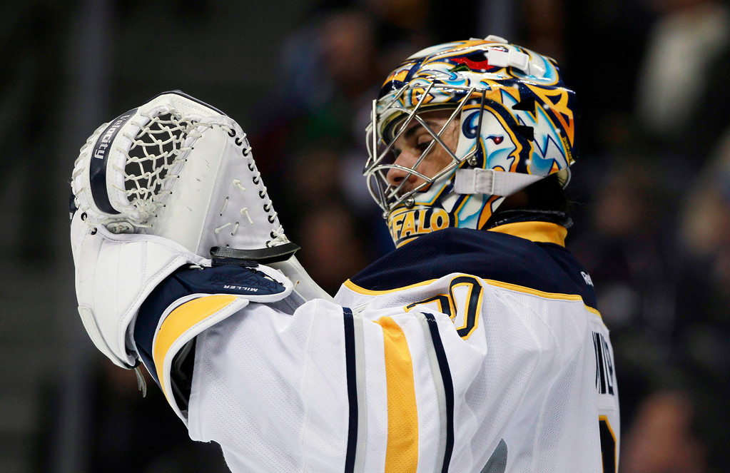 . Buffalo Sabres goalie Ryan Miller checks his glove after giving up goal to the Colorado Avalanche in the second period of an NHL hockey game in Denver, Saturday, Feb. 1, 2014. (AP Photo/David Zalubowski)