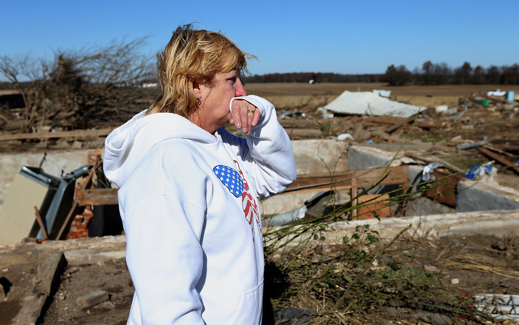 . Linda Agne looks over the damage where her former father-in-law Joseph Hoy and his sister Frances Hoy were killed Sunday on their farm outside New Minden, Ill.,  on Monday, Nov. 18, 2013. Dozens of tornadoes and intense thunderstorms swept across the U.S. Midwest on Sunday, unleashing powerful winds that flattened entire neighborhoods, flipped over cars and uprooted trees. (AP Photo/St. Louis Post-Dispatch, Robert Cohen)