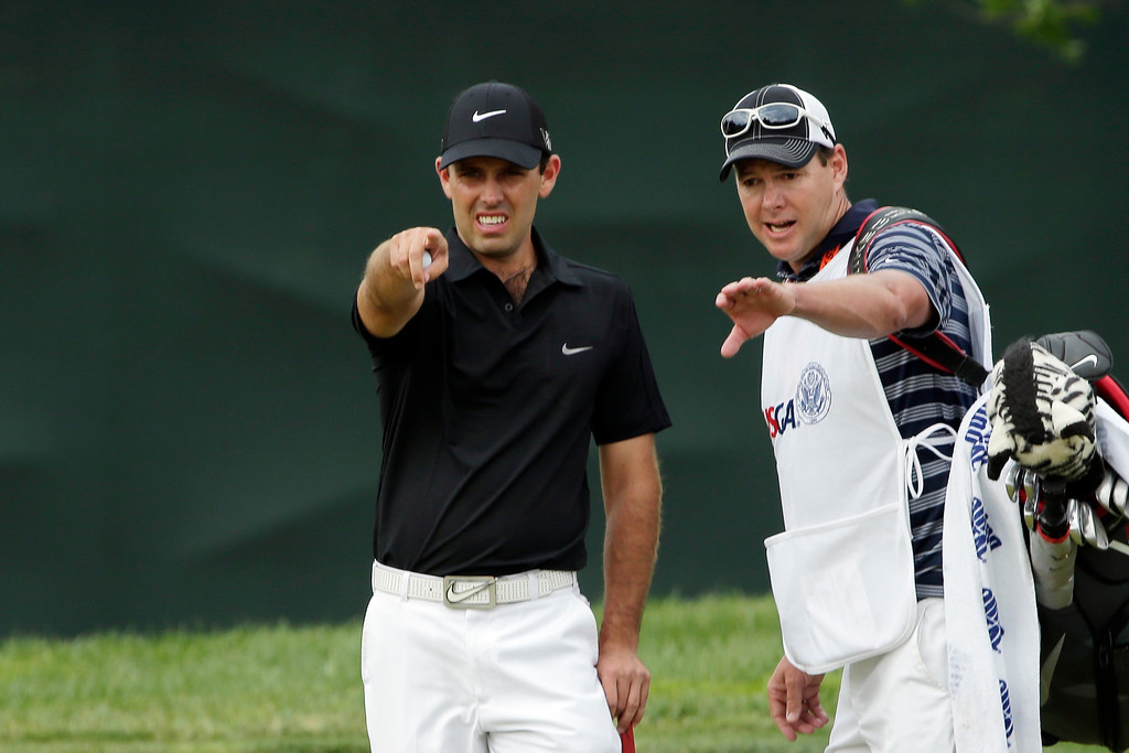 . Charl Schwartzel, left, of South Africa, and his caddie Glen Murray discuss his putt on the third green during the fourth round of the U.S. Open golf tournament at Merion Golf Club, Sunday, June 16, 2013, in Ardmore, Pa. (AP Photo/Charlie Riedel)