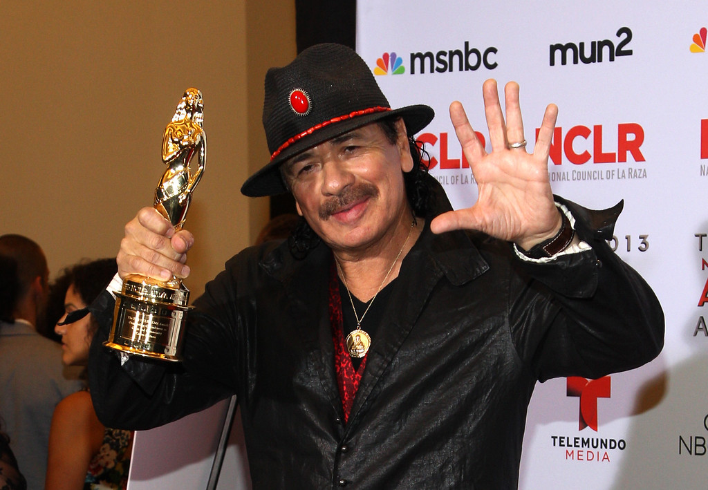 . Carlos Santana poses backstage with the award for outstanding commitment to cause and community: male at the NCLR ALMA Awards at the Pasadena Civic Auditorium on Friday, Sept. 27, 2013, in Pasadena, Calif. (Photo by Paul Hebert/Invision/AP Images)