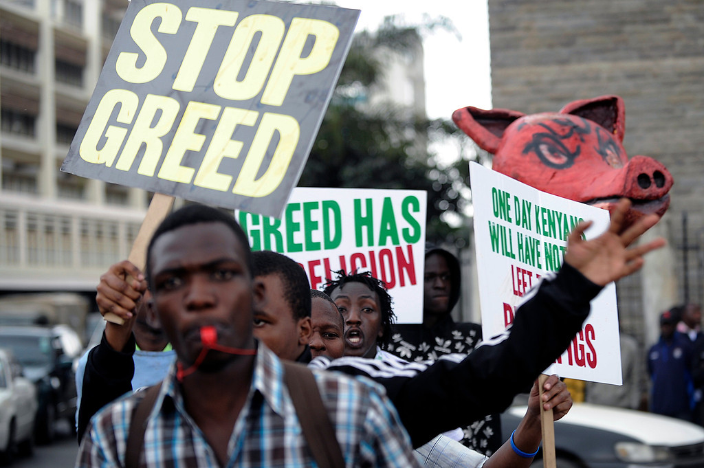 . Protesters hold placards during a demonstration outside the parliament after lawmakers voted themselves hefty salary increases on June 11, 2013 in Nairobi. The protestors had intended to occupy the parliament but were not allowed in by anti-riot police.  SIMON MAINA/AFP/Getty Images