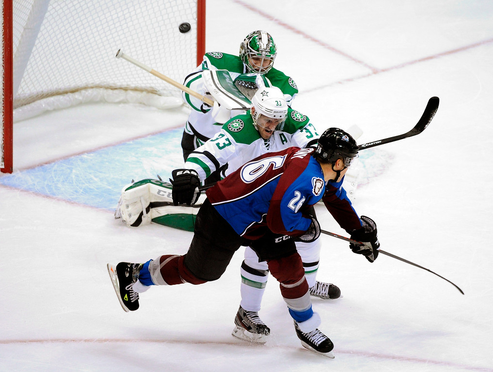 . Dallas defenseman Alex Goligoski (33) gave a shove to Colorado center Paul Stastny (26) in front of goalie Kari Lehtonen (32) in the first period.  Photo By Karl Gehring/The Denver Post