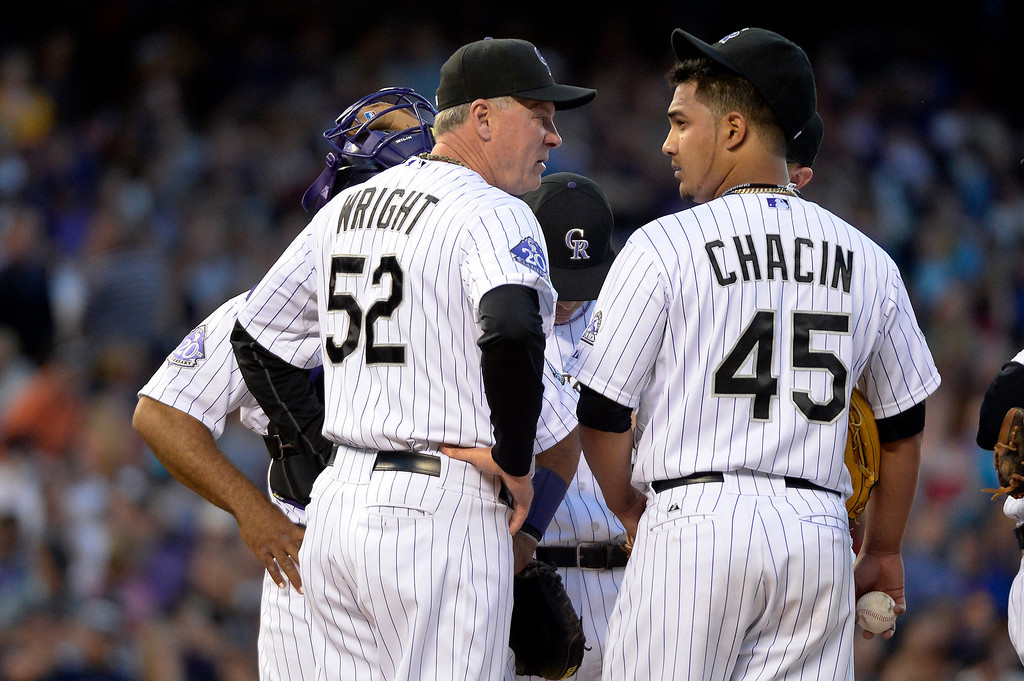 . Jim Wright (52) of the Colorado Rockies has a few words with Jhoulys Chacin (45) duirng a visit to the mound in the fourth inning against the San Francisco Giants May 16, 2013 at Coors Field. (Photo By John Leyba/The Denver Post)