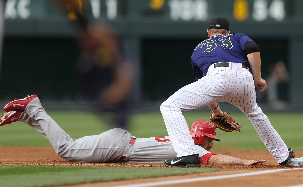. St. Louis Cardinals\' Matt Carpenter, left, dives back to first base as Colorado Rockies first baseman Justin Morneau fields the pickoff throw in the first inning of a baseball game in Denver on Monday, June 23, 2014. (AP Photo/David Zalubowski)