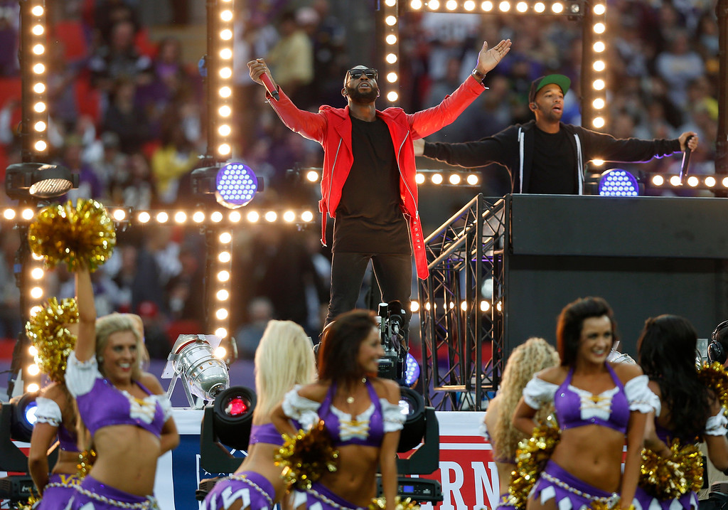 . British rapper Tinie Tempah, center, performs ahead of the NFL game between the Pittsburgh Steelers and Minnesota Vikings  at Wembley Stadium, London, Sunday, Sept. 29, 2013. (AP Photo/Sang Tan)