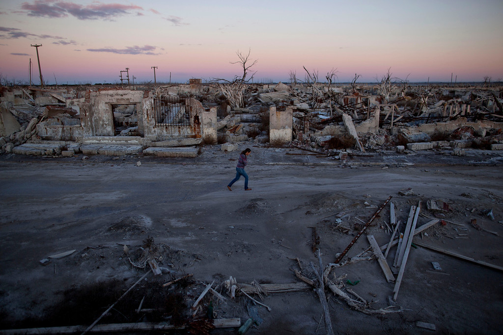 . In this May 6, 2013 photo, former resident and tourist guide Norma Berg walks by a street in Epecuen, a village that once was submerged in water in Argentina. People come to see the rusted hulks of automobiles and furniture, crumbled homes and broken appliances. They climb staircases that lead nowhere, and wander through a graveyard where the water toppled headstones and exposed tombs to the elements.   (AP Photo/Natacha Pisarenko)