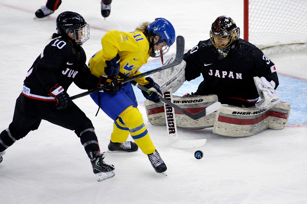 . Cecilia Ostberg of Sweden tries to gain control of the puck between Haruna Yoneyama and Goalkeeper Nana Fujimoto of Japan during the second period of the 2014 Winter Olympics women\'s ice hockey game at Shayba Arena, Sunday, Feb. 9, 2014, in Sochi, Russia. (AP Photo/Matt Slocum)