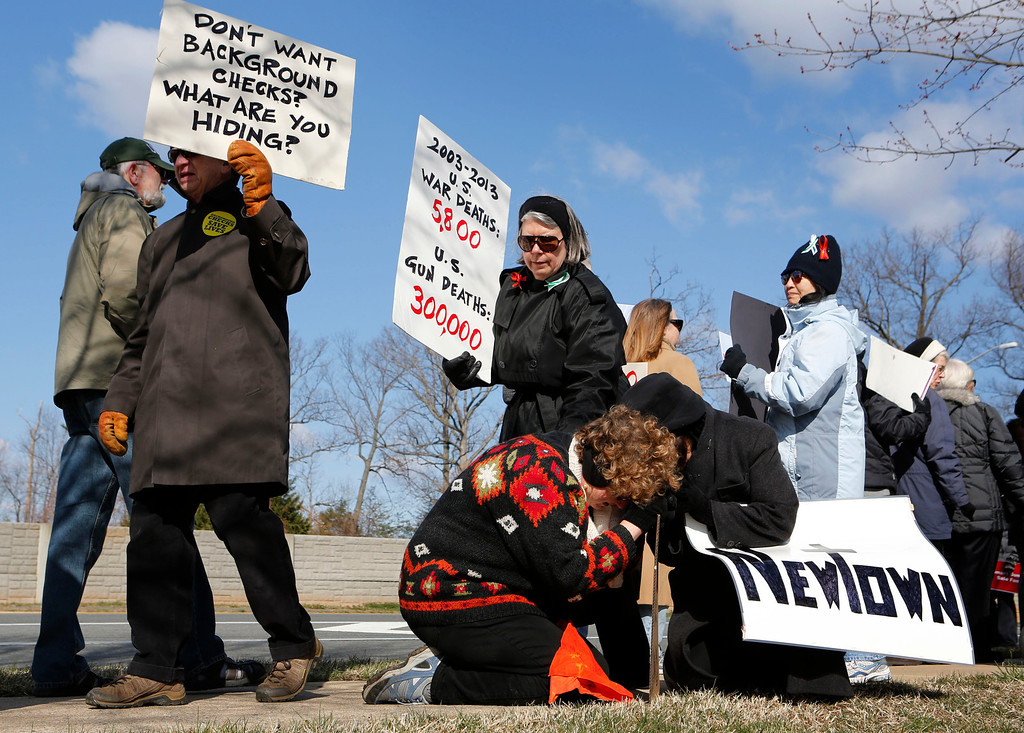 ". Louisa Davis (bottom L) and Sally Bawcombe kneel in front of the National Rifle Association headquarters during a rally by the activist group ""MomsRising\"" urging for sensible gun regulation in Fairfax, Virginia, March 14, 2013.      REUTERS/Larry Downing"