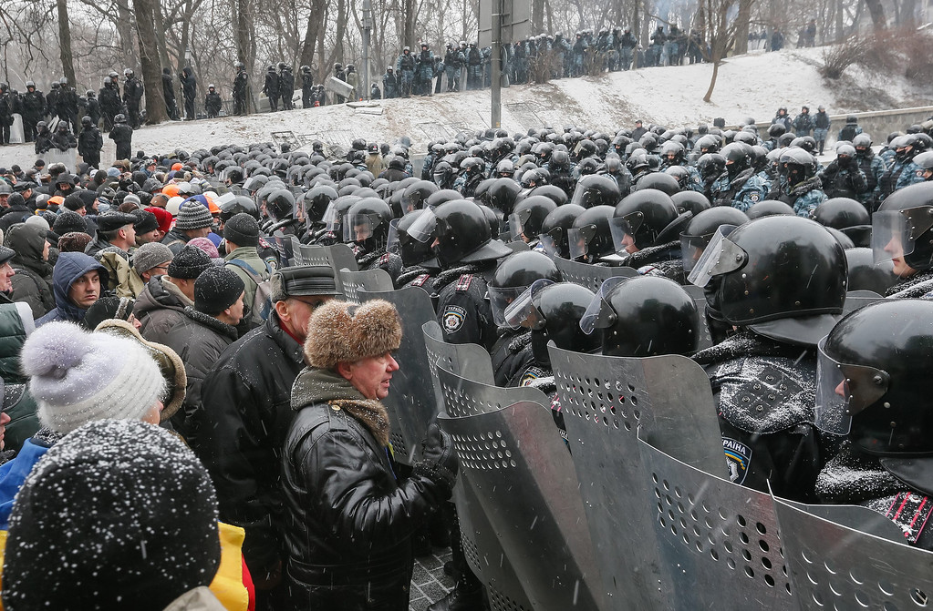 . Ukrainians stand against a line of riot police during an anti-government protest in downtown Kiev, Ukraine, 21 January 2014.  EPA/SERGEY DOLZHENKO