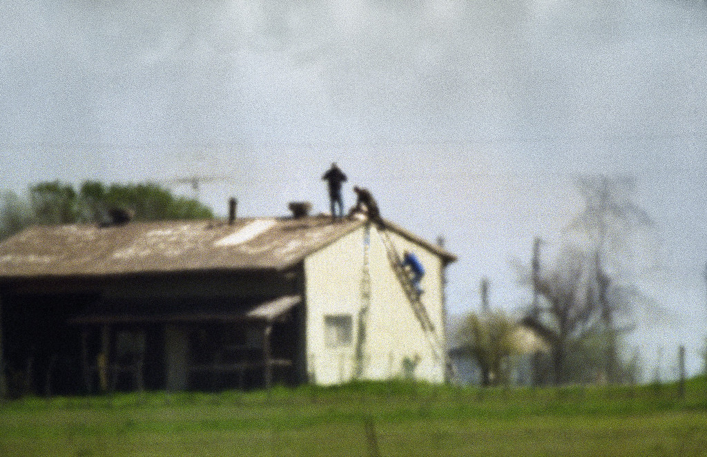 . Unidentified people climb on top of a barn adjacent to the Branch Davidian Compound near Waco, Texas on Thursday, April 8, 1993. An array of equipment had been left on the roof by federal authorities over the past 40 days of the cult standoff. (AP Photo/Susan Weems)