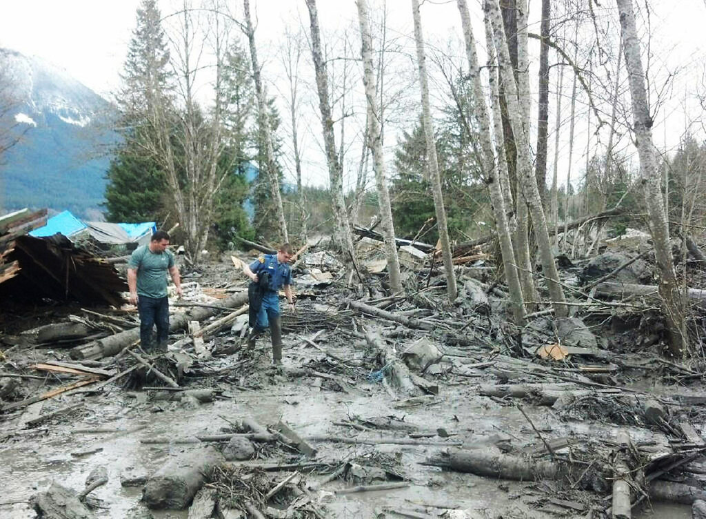 . In this handout from the Washington State Patrol, People examine debris after a mudslide March 22, 2014 in Snohomish County, Washington. According to reports, 18 people are still missing after a mudslide killed three and injured another eight. The mudslide is said to measure a square mile and 15 feet deep in places.  (Photo by Washington State Patrol via Getty Images)