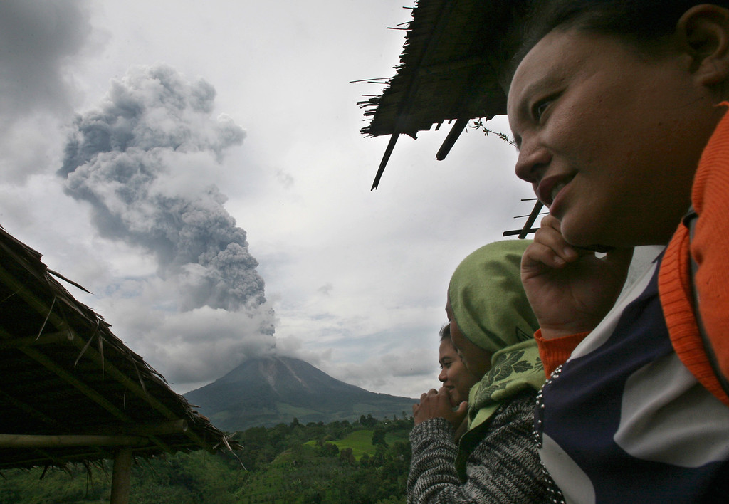 . Villagers watch as Mount Sinabung spews volcanic ash in Tiga Pancur, North Sumatra, Indonesia, Tuesday, Nov. 5, 2013.  (AP Photo/Binsar Bakkara)
