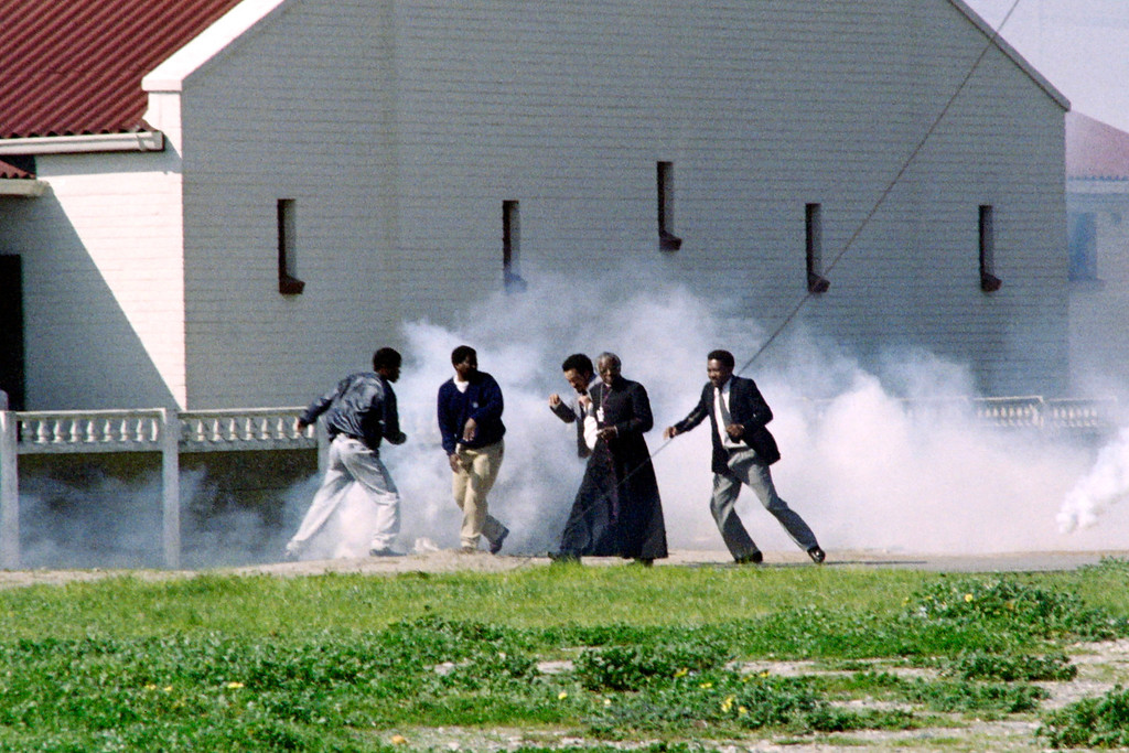 . Archibishop Desmond Tutu assited by Jakes Gerwel, rector of the University of the Western Cape, try to escape teargas fired by police, on August 23, 1989 after some of anti-apartheid activists emerged from a meeting in St Mary Magdalene, Gugulethu.          (RASHID LOMBARD/AFP/GettyImages)