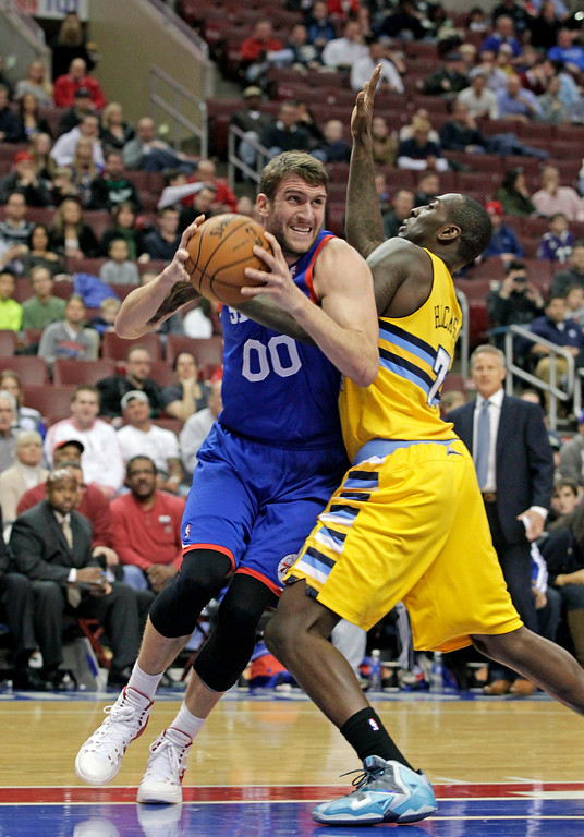 . Denver Nuggets\'  JJ Hickson (7) defends as Philadelphia 76ers\' Spencer Hawes (00) looks to pass in the first half of an NBA basketball game Saturday Dec. 7, 2013, in Philadelphia. The Nuggets won 103-92. (AP Photo/H. Rumph Jr)