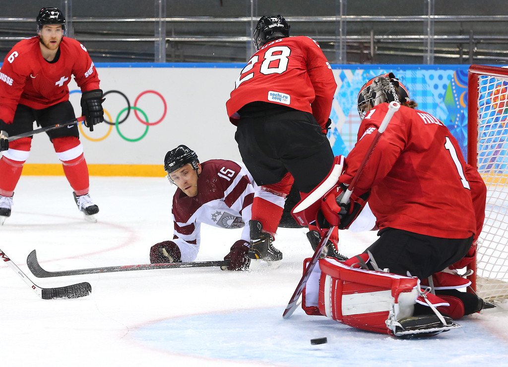 . SOCHI, RUSSIA - FEBRUARY 12: Martins Karsums #15 of Latvia dives while trying to shoot against Jonas Hiller #1 of Switzerland in the second period during the Men\'s Ice Hockey Preliminary Round Group C game on day five of the Sochi 2014 Winter Olympics at Shayba Arena on February 12, 2014 in Sochi, Russia.  (Photo by Martin Rose/Getty Images)