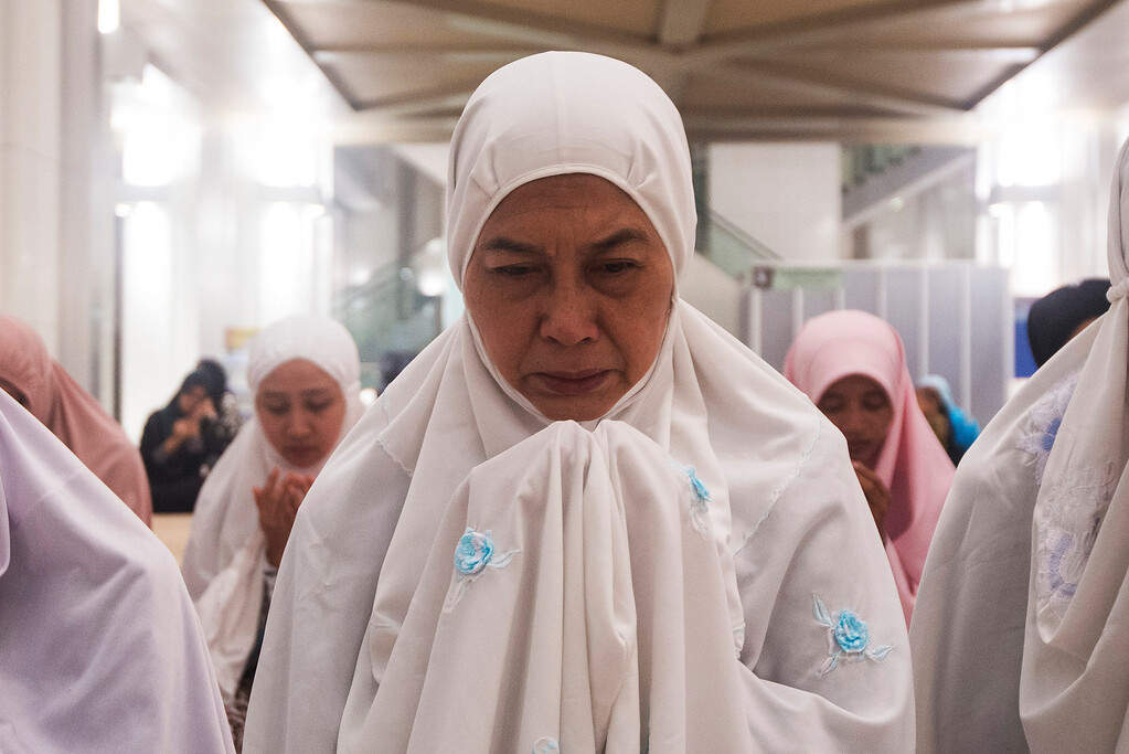 . A Malaysian Muslim woman offers a special prayer for passengers aboard a missing plane, at a mosque in Putrajaya, Malaysia, Sunday, March 9, 2014. Military radar indicates that the missing Boeing 777 jet may have turned back before vanishing, Malaysia\'s air force chief said Sunday as authorities were investigating up to four passengers with suspicious identifications. (AP Photo/Joshua Paul)