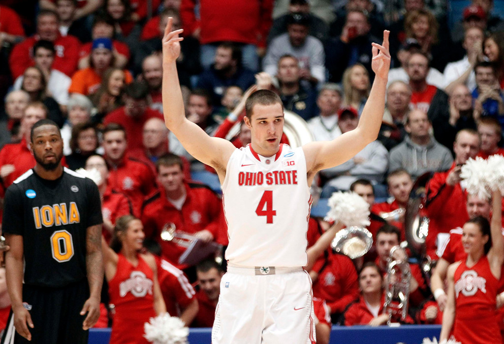 . Ohio State Buckeyes guard Aaron Craft celebrates after scoring a basket as Iona Gaels forward Taaj Ridley (L) looks on during the first half of their second round NCAA tournament basketball game in Dayton, Ohio March 22, 2013.  REUTERS/Matt Sullivan