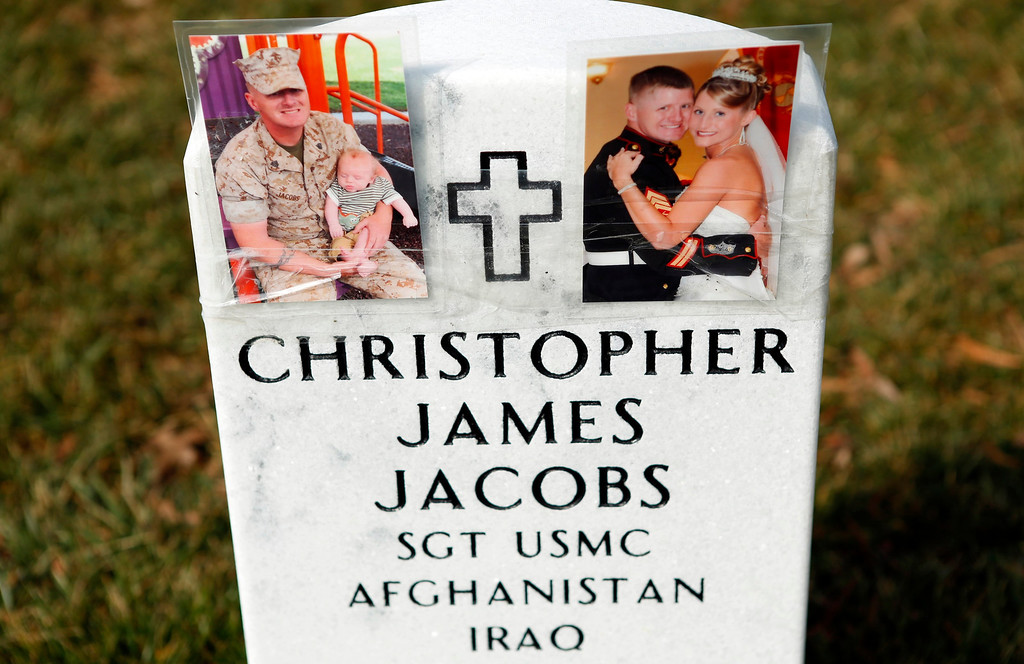 . Photos are seen on a headstone in Section 60 at Arlington National Cemetery in Virginia, March 13, 2013. Section 60 contains graves of soldiers from the wars in Iraq and Afghanistan. Picture taken March 13, 2013. REUTERS/Kevin Lamarque