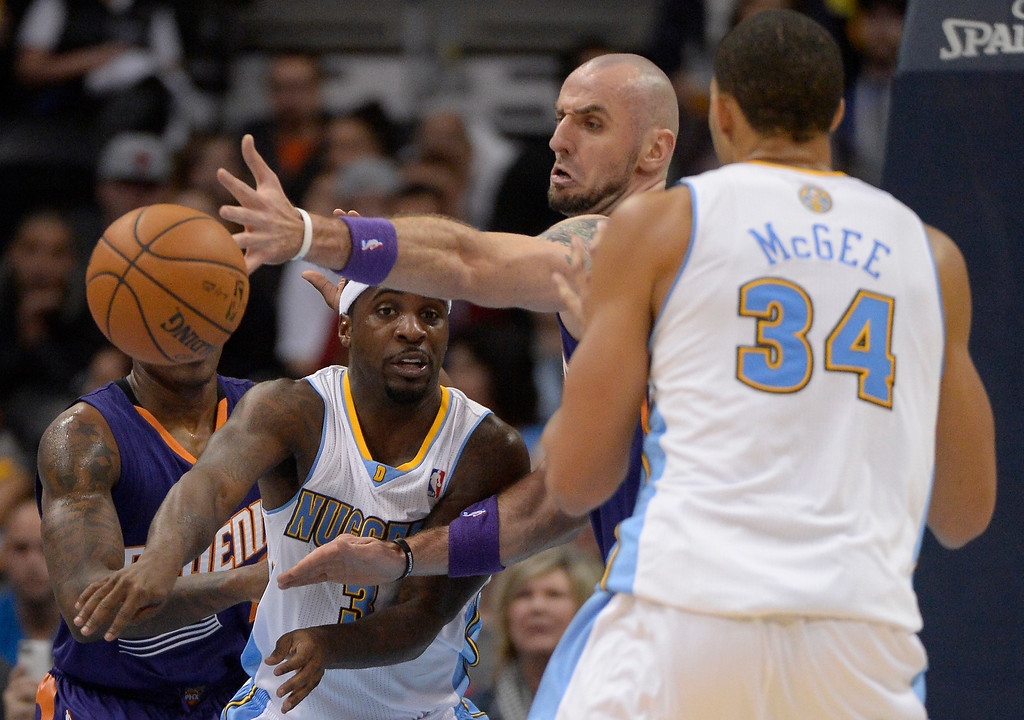 . Denver Nuggets point guard Ty Lawson (3) gets a pass off past Phoenix Suns center Marcin Gortat (4) during the fourth quarter October 23, 2013 at Pepsi Center. (Photo By John Leyba/The Denver Post)