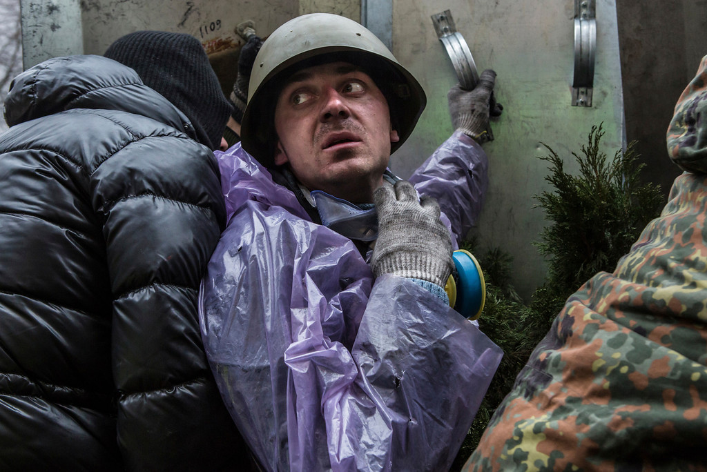 . An anti-government protester takes cover from suspected sniper fire near the Hotel Ukraine on February 20, 2014 in Kiev, Ukraine.  (Photo by Brendan Hoffman/Getty Images)