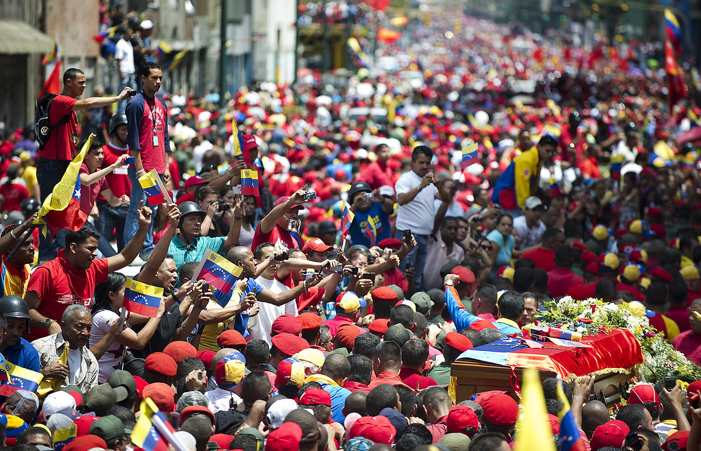 . The hearse carrying the coffin of Venezuelan President Hugo Chavez makes its way to the Military Academy amid thousands of supporters, on March 6, 2013, in Caracas. The flag-draped coffin of Venezuelan leader Hugo Chavez was borne through throngs of weeping supporters on Wednesday as a nation bade farewell to the firebrand leftist who led them for 14 years. AFP PHOTO/Juan BARRETOJUAN BARRETO/AFP/Getty Images