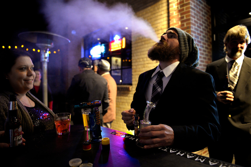 . DENVER, CO. - December 31: Canna Caregivers general manager Amy Reynolds watches as her fiancee Mike Cadwell blows out a large hit of hash at the Prohibition is Over! party at Casselman\'s Bar and Venue by The Hemp Connoisseur & Mahatma Extreme Concentrates December 31, 2013 Denver, CO. (Photo By Joe Amon/The Denver Post)