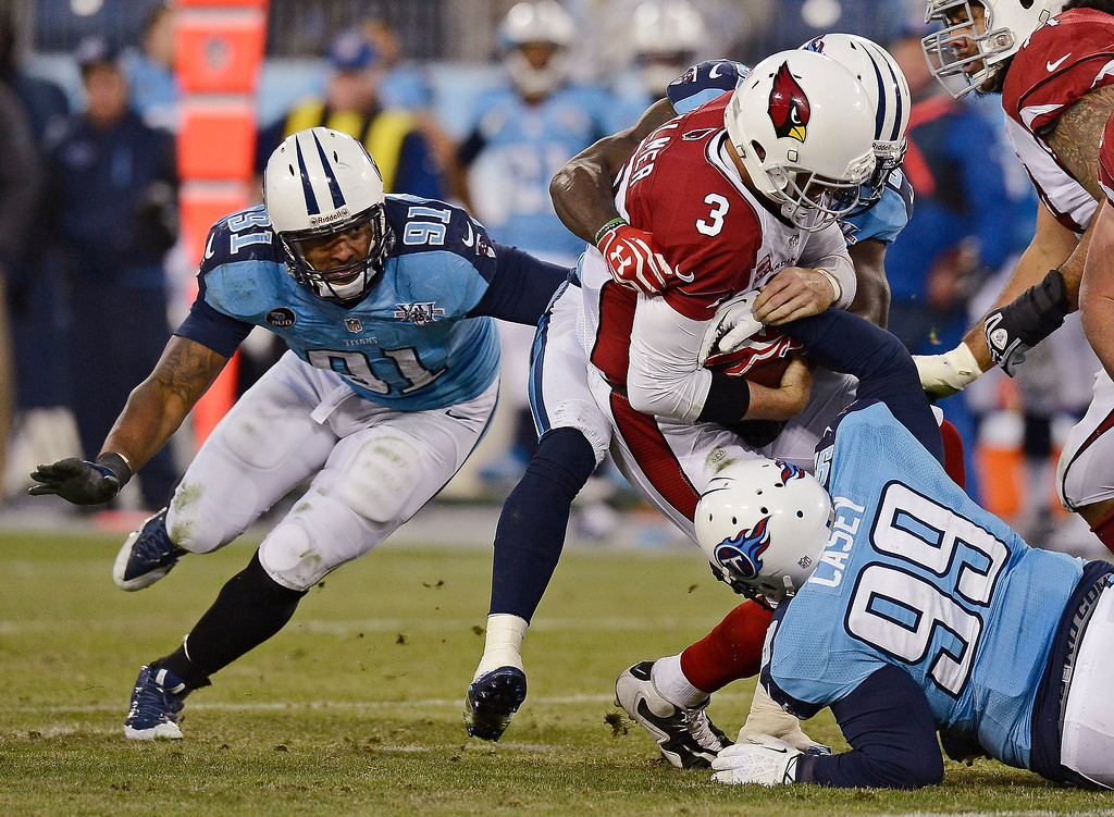 Description of . Arizona Cardinals quarterback Carson Palmer (3) is sacked for a 7-yard loss by Tennessee Titans defensive tackle Jurrell Casey (99) and Derrick Morgan (91) in the second quarter of an NFL football game Sunday, Dec. 15, 2013, in Nashville, Tenn. (AP Photo/Mark Zaleski)