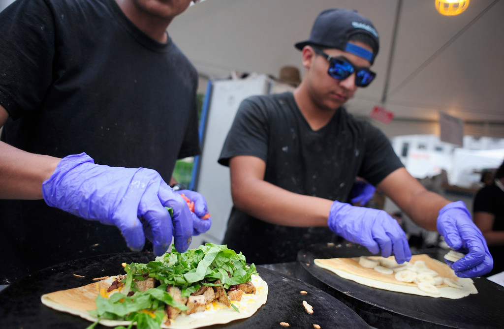 . David Rangelreyes, 21, (L) and Damian Lucero, 17 (R), prepare crêpes at the Crêpes & Company booth during the A Taste of Colorado festival at Civic Center Park in Denver, Colorado, Saturday, August 30, 2014. (Photo By Brenden Neville / Special to The Denver Post)