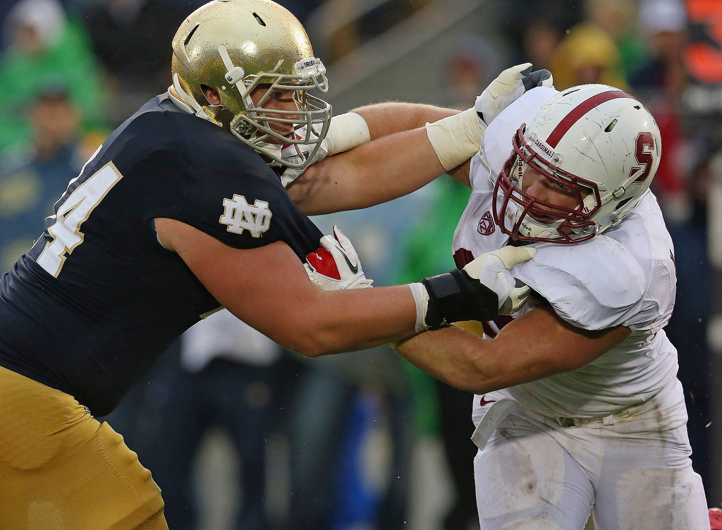 . Christian Lombard #74 of the Notre Dame Fighting Irish blocks Kevin Anderson #48 of the Standford Cardinal at Notre Dame Stadium on October 13, 2012 in South Bend, Indiana. Notre Dame defeated Stanford 20-13 in overtime.  (Photo by Jonathan Daniel/Getty Images)