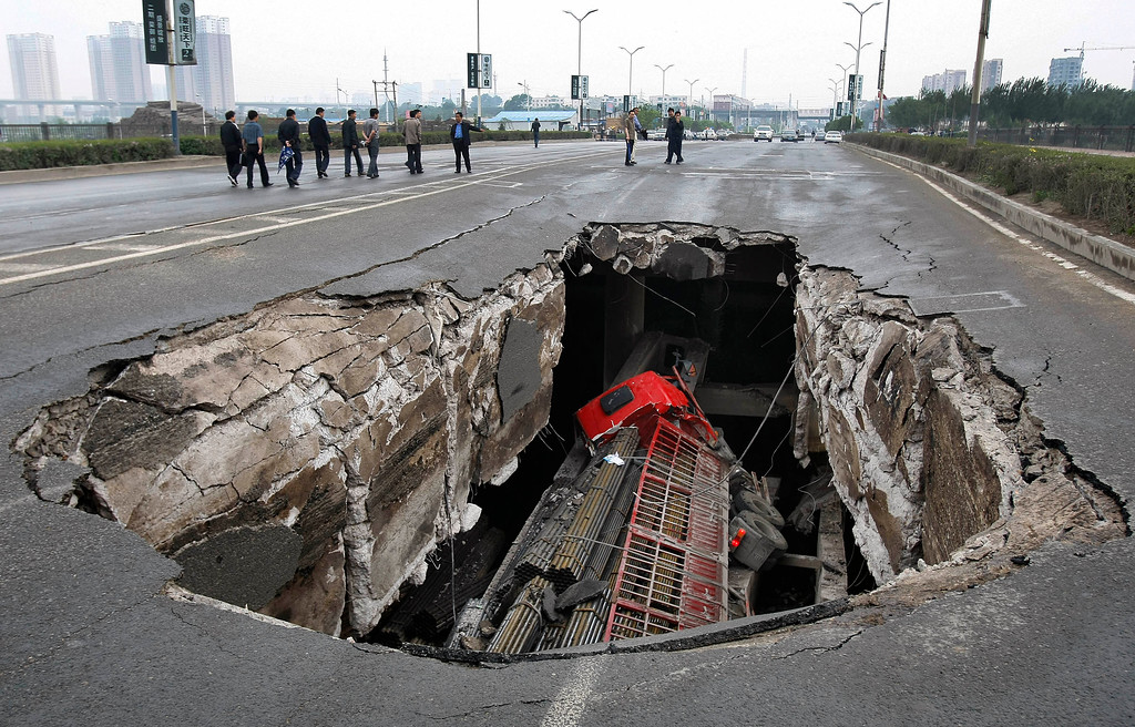 . A truck is seen in a hole after part of the structure of a bridge collapsed into a river in Changchun, Jilin province May 29, 2011. Two truck passengers were injured, while the cause of the accident is still under investigation, local media reported. Picture taken May 29, 2011. REUTERS/China Daily