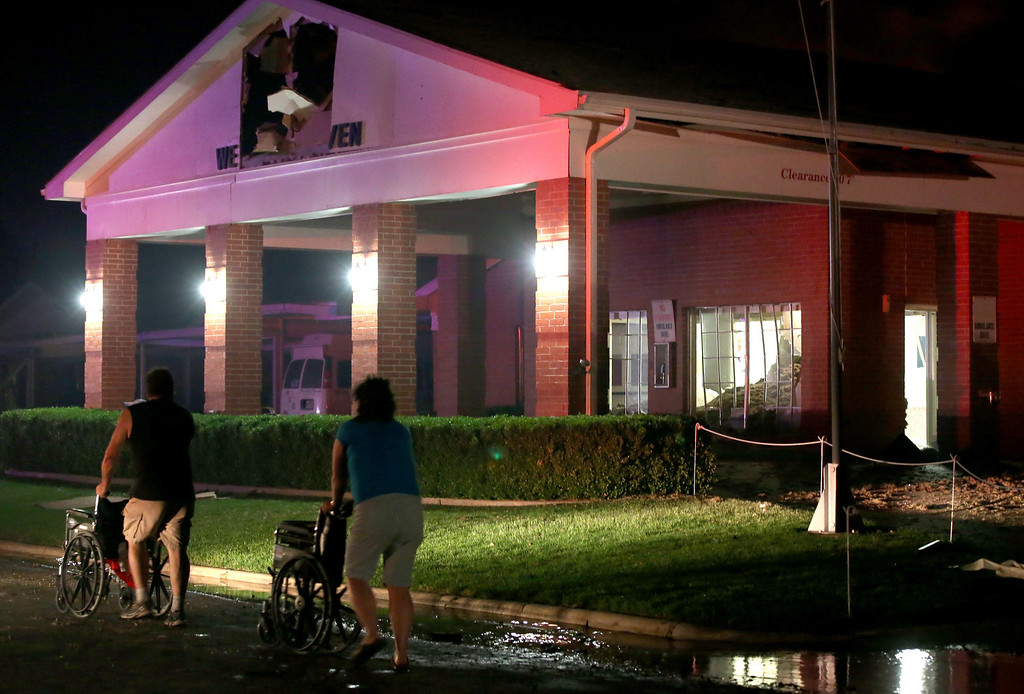. Persons are seen pushing wheel chairs in front of a damaged nursing home following an explosion at a nearby fertilizer plant Wednesday, April 17, 2013, in West, Texas. An explosion at a fertilizer plant near Waco caused numerous injuries and sent flames shooting high into the night sky on Wednesday.(AP Photo/ Waco Tribune Herald, Rod Aydelotte)