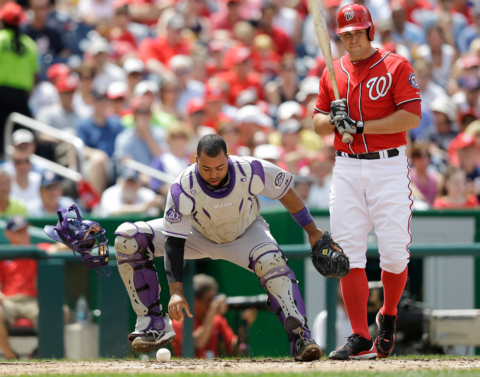 . Colorado Rockies catcher Wilin Rosario chases the loose ball as Washington Nationals relief pitcher Craig Stammen (35) stands by during the fourth inning of a baseball game at Nationals Park, Sunday, June 23, 2013, in Washington. The Rockies won 7-6. (AP Photo/Carolyn Kaster)