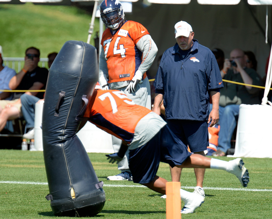 . Denver Broncos offensive line coach Dave Magazu watches Denver Broncos tackle Chris Clark (75) hit the blocking dummy during practice August 19, 2013 at Dove Valley (Photo by John Leyba/The Denver Post)