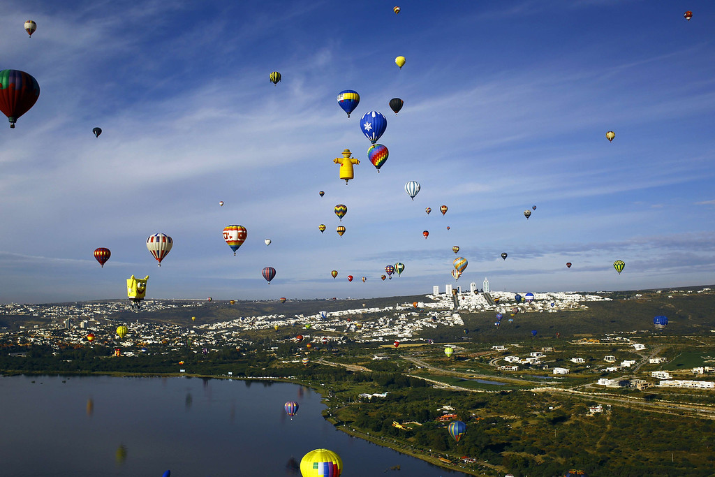 . Hot air balloons fly over a lake during the International Balloon Festival at the Metropolitan Park in Leon, Guanajuato state, Mexico on November  15, 2013.  AFP PHOTO/Hector GUERRERO/AFP/Getty Images