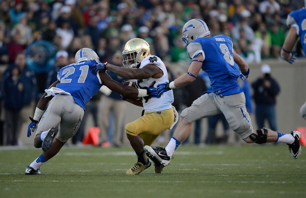 . COLORADO SPRINGS, CO - OCTOBER 26: Notre Dame RB, Tarean Folston, center, gains yardage against Air Force defenders, Christian Spears, left, and Jared Jones, in the third quarter at Falcon Stadium, Saturday afternoon, October 26, 2013. (Photo By Andy Cross/The Denver Post)