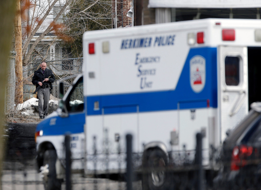 . A law enforcement officer walks along Main Street in Herkimer, N.Y., while searching for a suspect in two shootings that killed four and injured at least two on, Wednesday, March 13, 2013.  (AP Photo/Mike Groll)