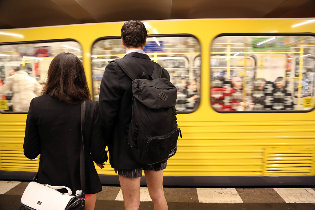 . Participants of the No Pants Subway Ride hold hands as a train approaches on January 12, 2014 in Berlin, Germany. The annual event, in which participants board a subway car in January while not wearing any pants while behaving as though they do not know each other, began as a joke by the public prank group Improv Everywhere in New York City and has since spread around the world, with enthusiasts in around 60 cities and 29 countries across the globe, according to the organization\'s site.  (Photo by Adam Berry/Getty Images)
