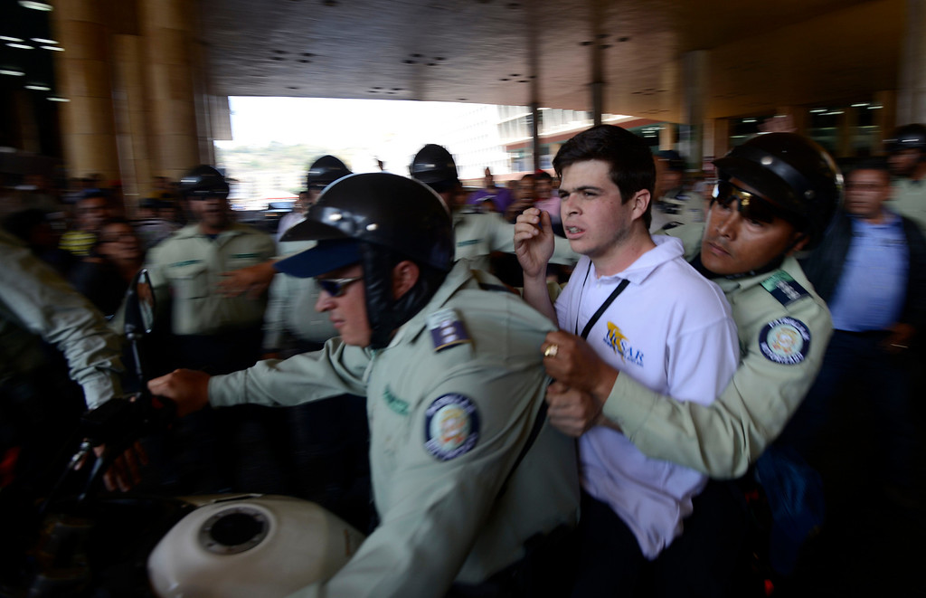 ". Members of the National Police take an opposition student into custody during a demonstration in front of the Electoral National Centre in Caracas on March 4, 2013. On Sunday, hundreds of opposition protesters chanting ""We want the truth\"", marched in Caracas demanding that the government reveal more about the health of cancer-stricken President Hugo Chavez. JUAN BARRETO/AFP/Getty Images"