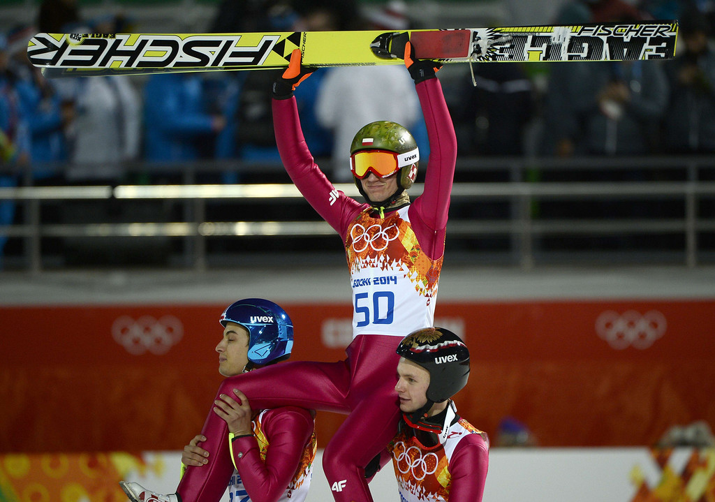 . Poland\'s Kamil Stoch (C) is carried by Poland\'s Maciej Kot (L) and Poland\'s Jan Ziobro (R) while celebrating his gold medal in the finish area of the Men\'s Ski Jumping Large Hill Individual Final Round at the RusSki Gorki Jumping Center during the Sochi Winter Olympics on February 15, 2014, in Rosa Khutor. PIERRE-PHILIPPE MARCOU/AFP/Getty Images