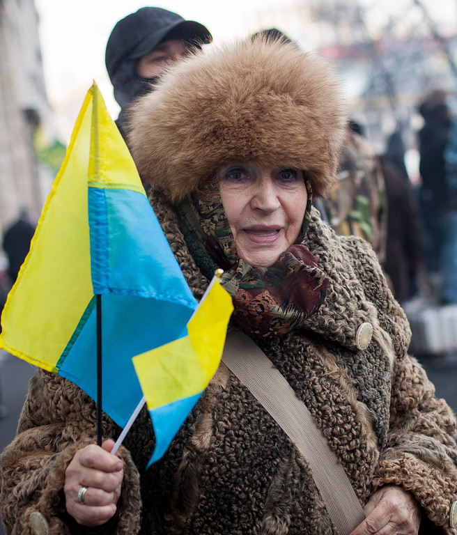 . An anti-government protestor holding Ukrainian flags walks Dynamo Stadium on January 25, 2014 in Kiev, Ukraine. Violent protests in Ukraine have spread beyond the capital as President Viktor Yanukovych held crisis talks with three key opposition leaders. (Photo by Rob Stothard/Getty Images)