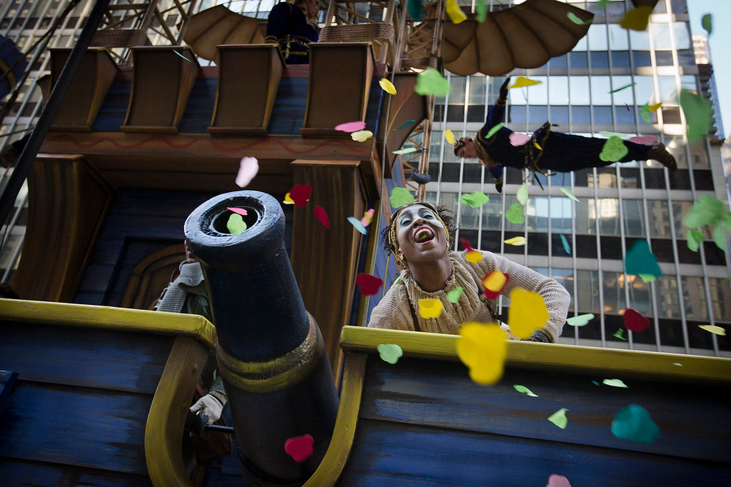 . A performer on the Cirque du Soleil float cheers after firing confetti into the crowd on 6th Avenue during the 87th Annual Macy\'s Thanksgiving Day Parade, Thursday, Nov. 28, 2013, in New York. After fears the balloons could be grounded if sustained winds exceeded 23 mph, Snoopy, Spider-Man and the rest of the iconic balloons received the all-clear from the New York Police Department to fly between Manhattan skyscrapers on Thursday. (AP Photo/John Minchillo)