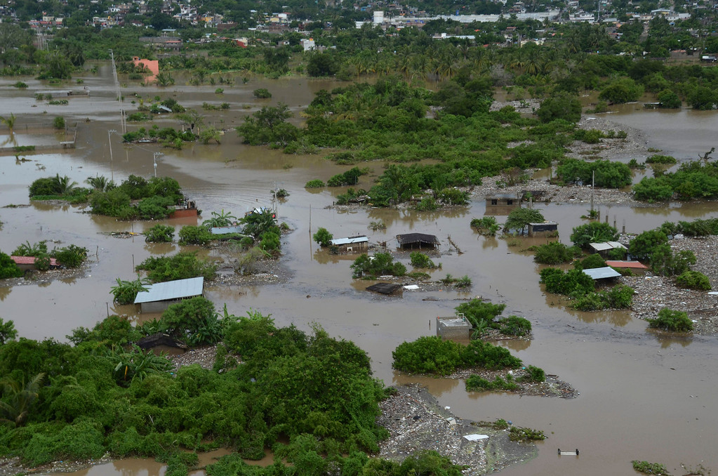 . A low income neighborhood is covered by floodwaters caused by Tropical Storm Manuel in Acapulco, Mexico, Tuesday, Sept. 17, 2013. The death toll rose to 47 Tuesday from the unusual one-two punch of a tropical storm and a hurricane hitting Mexico at nearly the same time. Authorities scrambled to get help into, and stranded tourists out of, the cutoff resort city of Acapulco. (AP Photo/Bernandino Hernandez)
