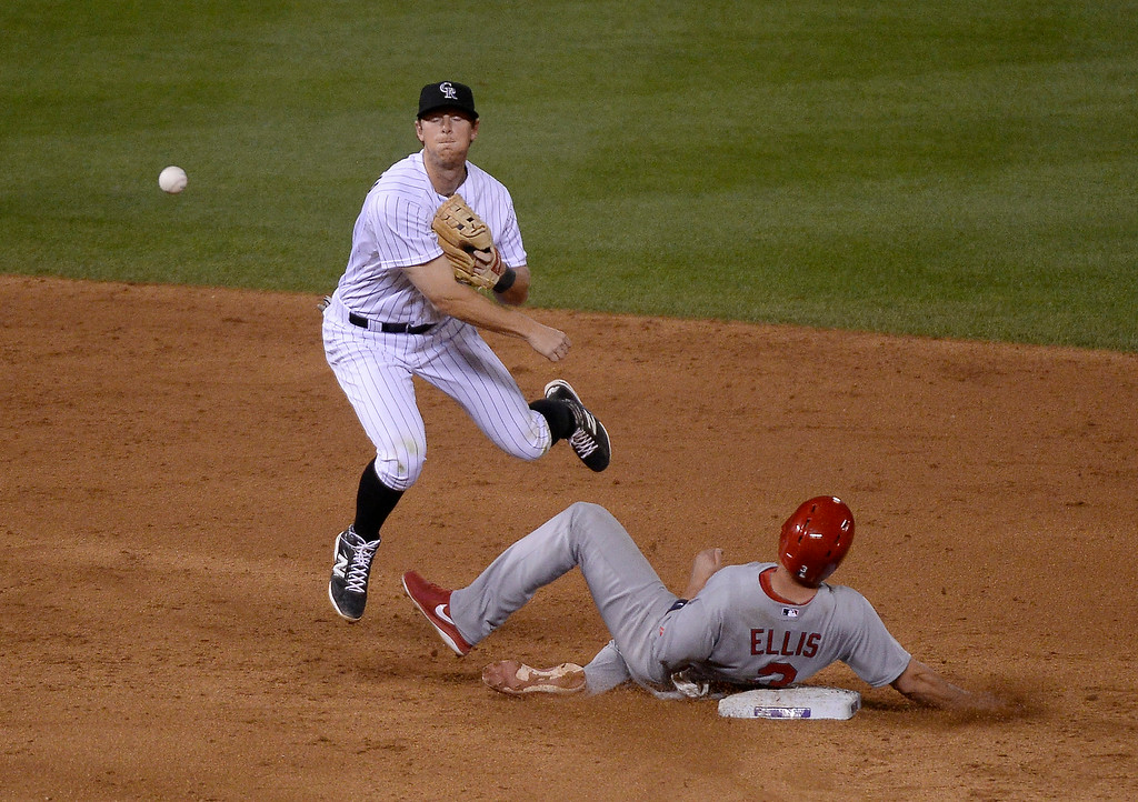 . DENVER, CO - JUNE 24: Colorado Rockies DJ LeMahieu (9) gets the force on St. Louis Cardinals second baseman Mark Ellis (3) as he throws over to first base to get St. Louis Cardinals catcher Tony Cruz (48) for the double play during the sixth inning June 24, 2014 at Coors Field. (Photo by John Leyba/The Denver Post)