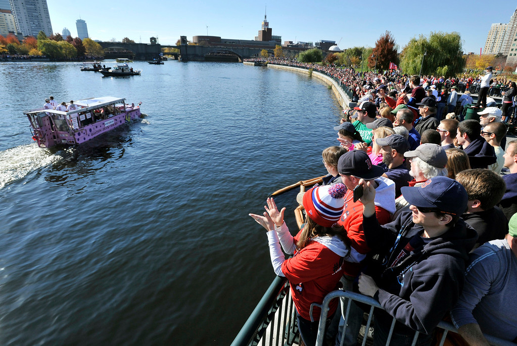 . Fans gathered along the Charles River as Boston Red Sox players ride past on amphibious duck boats during the baseball team\'s World Series victory parade Saturday, Nov. 2, 2013, in Cambridge, Mass. (AP Photo/Josh Reynolds)