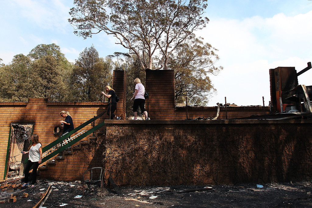 . Members of the Rogers family inspect the damage to their destroyed home on October 18, 2013 in Winmalee, Australia.  (Photo by Lisa Maree Williams/Getty Images)